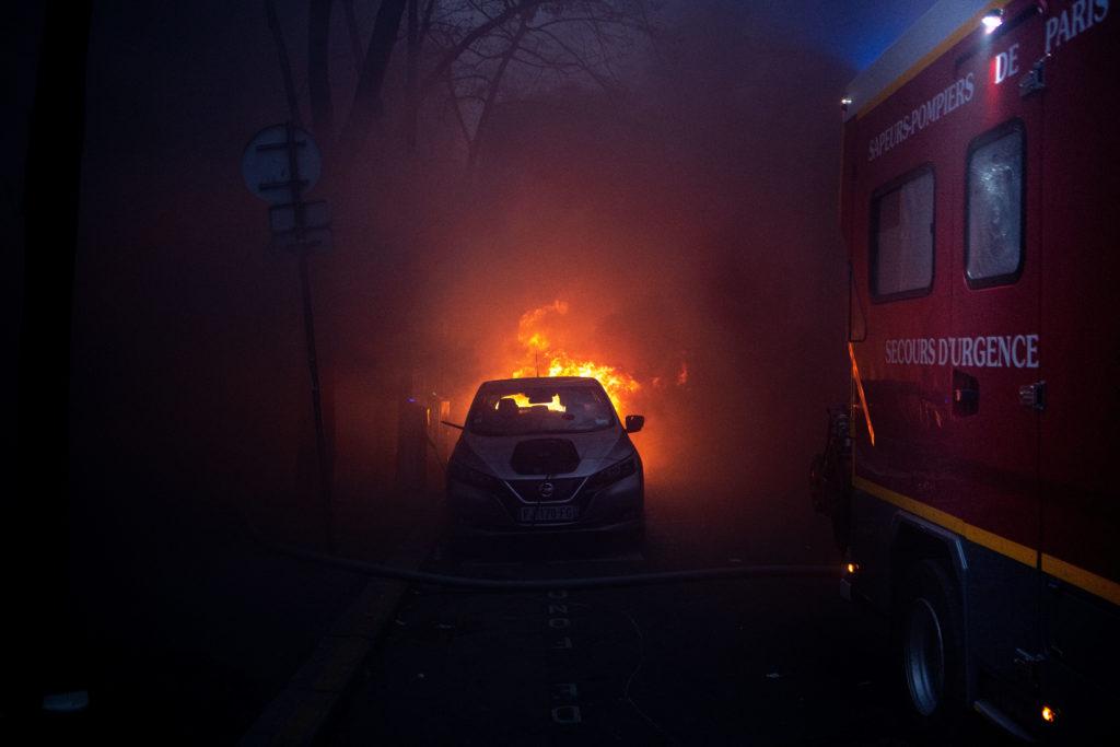 Une voiture en feu et un camion de pompier dans la fumée d'une agence bancaire incendiée durant la manifestation du 5 décembre contre la proposition de loi dite Sécurité globale à Paris