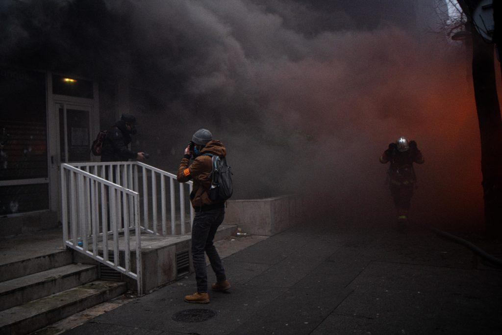 Un photographe en plein travail face à un incendie d'une agence du crédit mutuel avenue Gambetta à Paris, tandis qu'un pompier traverse la fumée pour aller combattre l'incendie. lors de la manifestation du 5 décembre contre le projet de loi dit Sécurité globale.