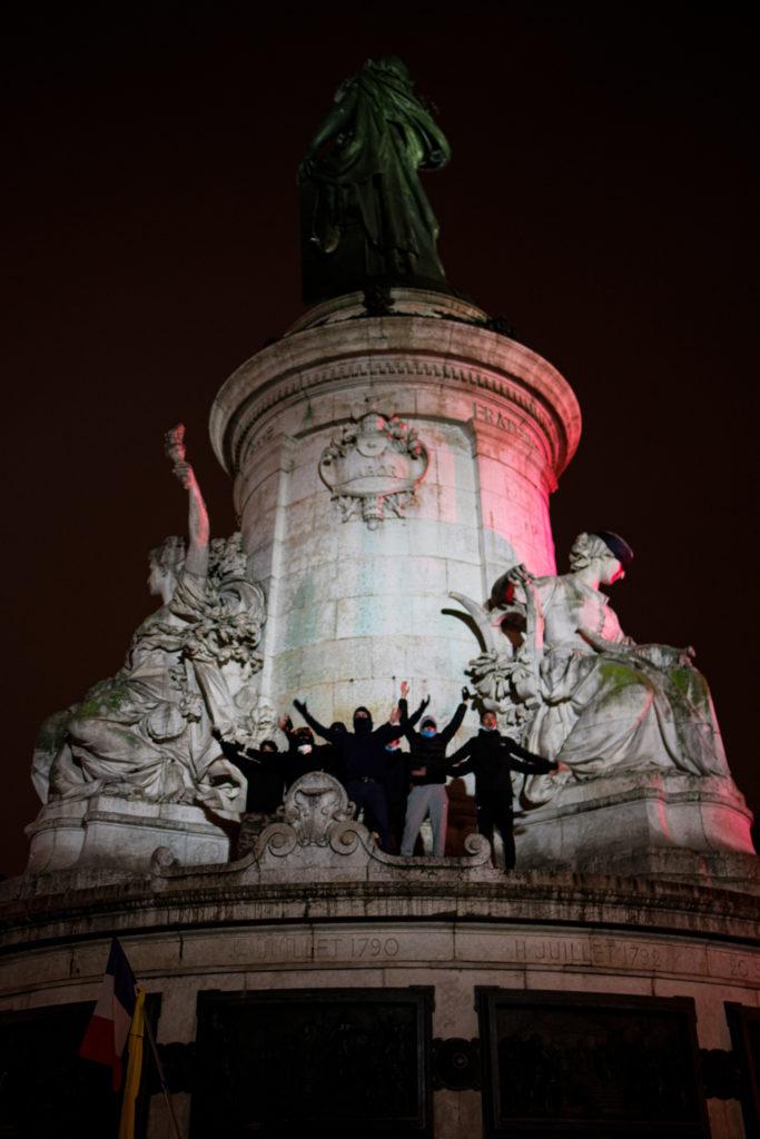 """Des militants antifascistes ayant gravis la fontaine de la place de la République à Paris lancent un """"clapping""""  durant la manifestation contre la proposition de loi dite Sécurité Globale le 5 décembre 2020."""