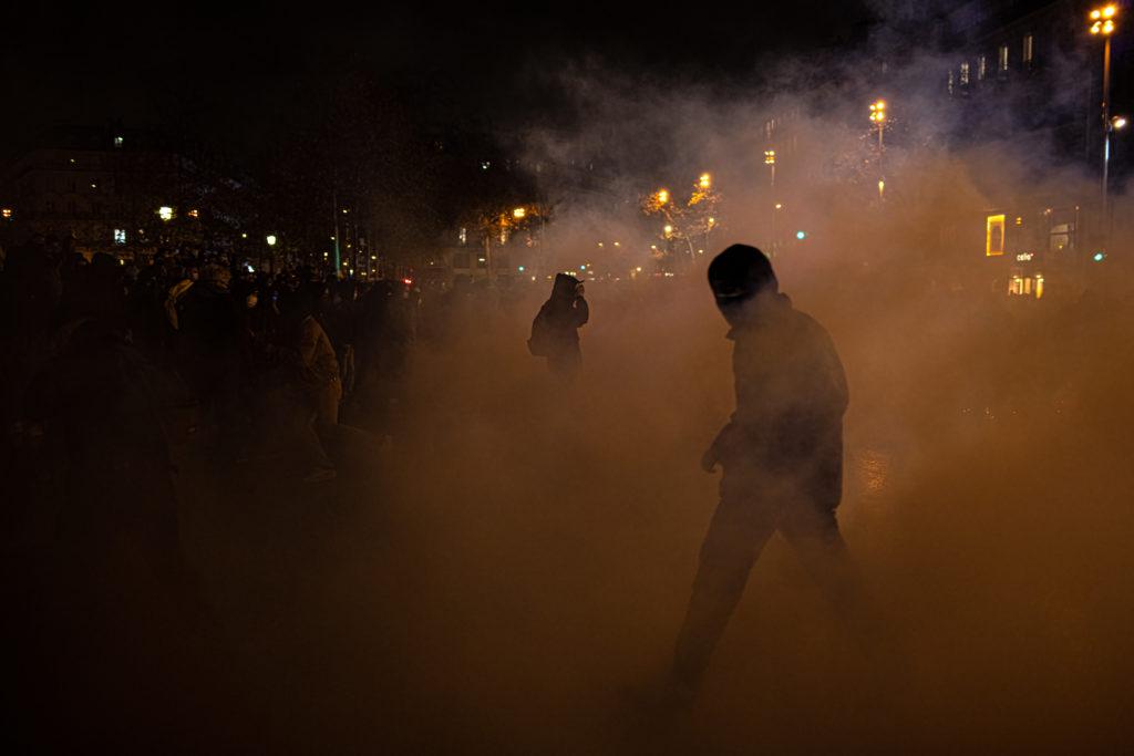 Un homme sort d'un nuage de gaz lacrymogène place de la République à Paris lors d'affrontements entre manifestants et policiers à la fin de la manifestation contre la proposition de loi dite Sécurité Globale le 5 décembre 2020.