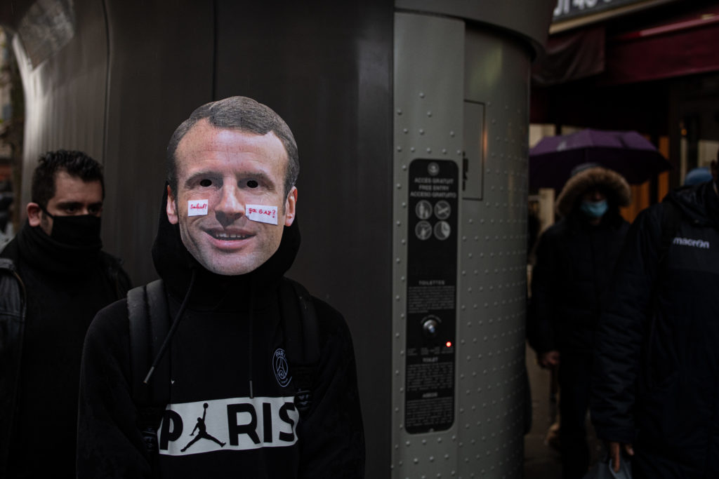 """Un manifestant porte un masque représentant le visage d'Emmanuel Macron avec le message """"salut ça gaz?"""", lors de la manifestation contre la proposition de loi dite Sécurité Globale le 12 décembre 2020."""