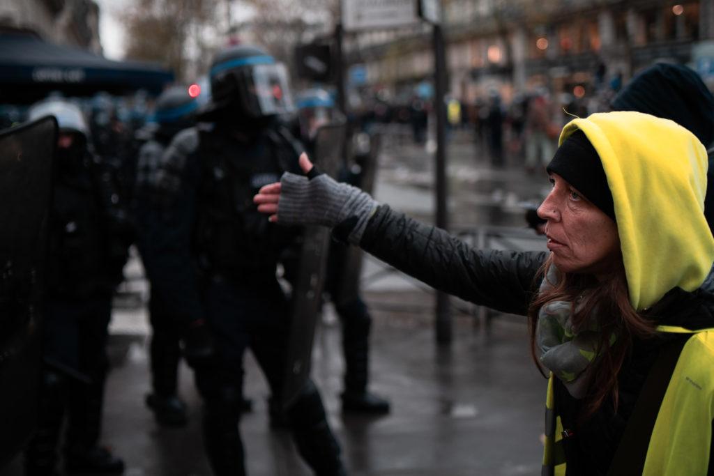 """Une manifestante arborant un gilet jaune demande ux policier si """"ils n'ont pas honte de charger gratuitement le cortège"""" lors de la manifestation contre la proposition de loi dite Sécurité Globale le 12 décembre 2020."""