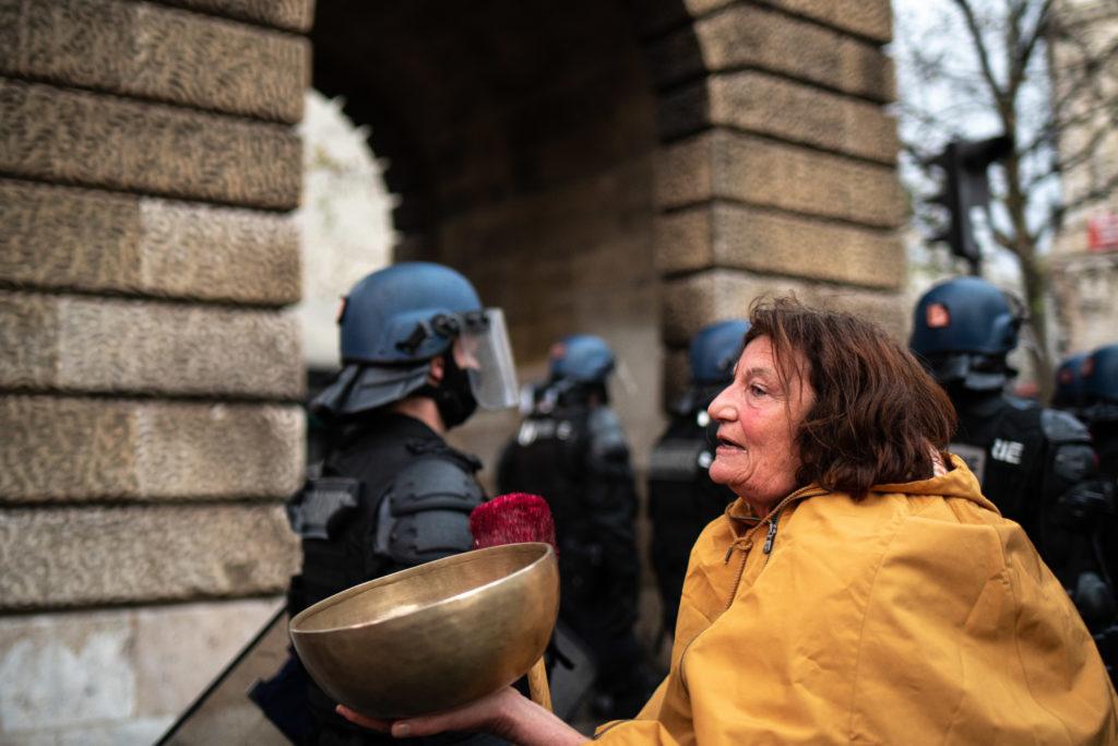 """Une femme joue du bol tibétain """"pour apporter la paix et appaiser les âmes"""" lors de la manifestation contre la proposition de loi dite Sécurité Globale le 12 décembre 2020."""