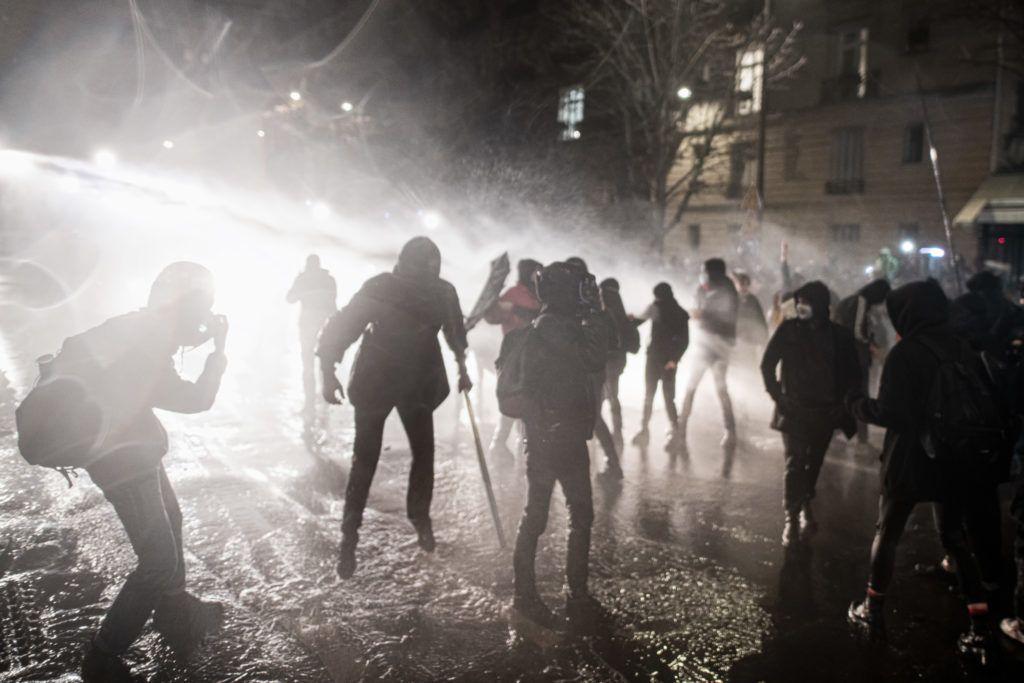 Le 21 novembre 2020, une personnne semble en lévitation dos à la police qui asperge les manifestants avec un canon à eau à la fin de la manifestation contre la proposition de loi Sécurité globale