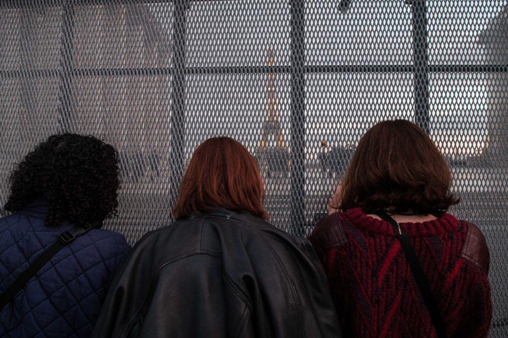 Le 21 novembre 2020, un groupe de femmes prend des photos des CRS sur le parvis des droits de l'homme derrière une barrière en métal, pendant la manifestation contre la proposition de loi Sécurité globale