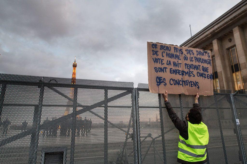 Le 21 novembre 2020, un homme brandit une pancarte mettant en cause l'heure choisie pour le vote de l'article 24 de la proposition de loi Sécurité globale face aux CRS sur le parvis des droits de l'homme derrière une barrière en métal.