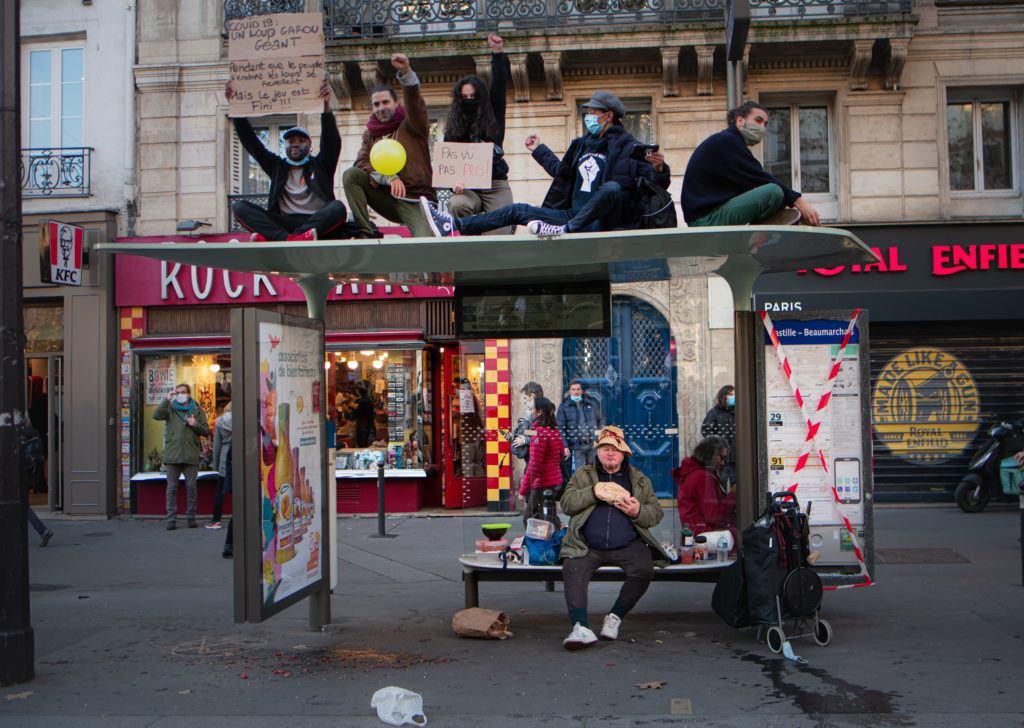 Des manifestants sur un abri-bus place de la bastille brandissant des pancartes et un homme sans abri en plein repas - 28 novembre 2020 - Manifestation contre le projet de loi Sécurité Globale