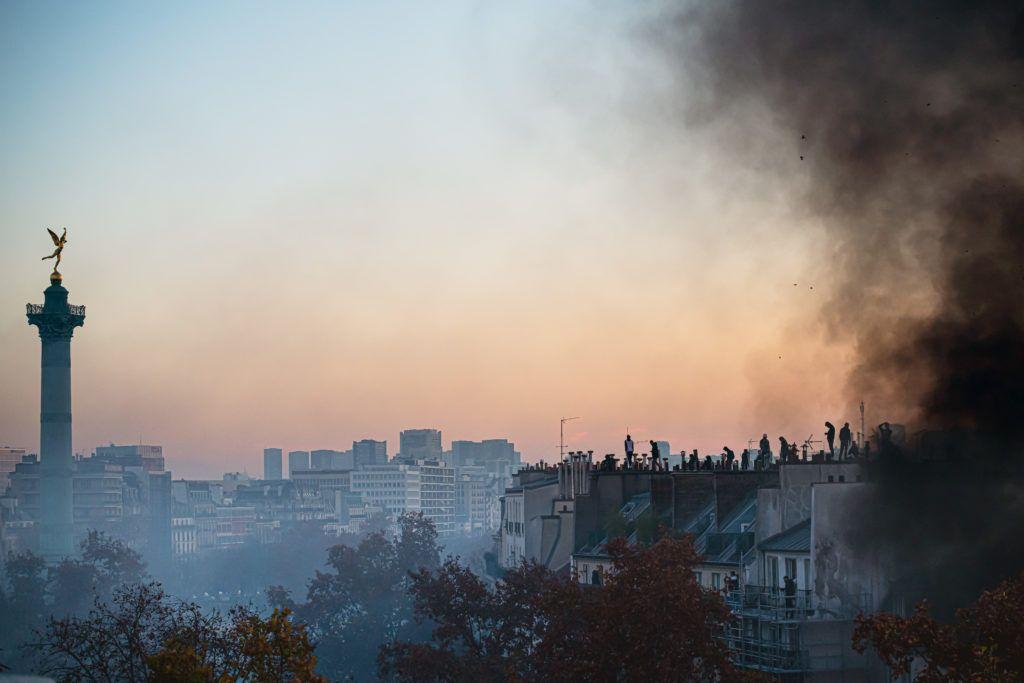 Plusieurs personnes sur un toit au dessus de la place de la bastille face au génie, dans la fumée des feus allumés durant la manifestation - 28 novembre 2020 - Manifestation contre le projet de loi Sécurité Globale - Paris