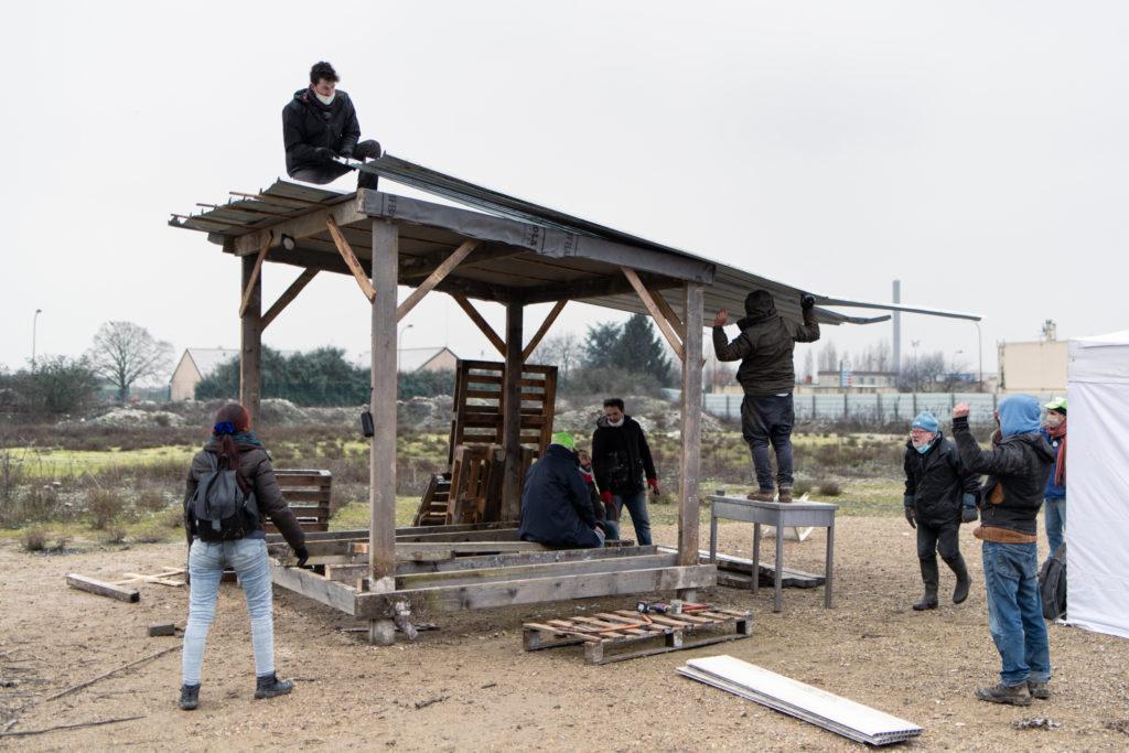 Des militants montent la dernière tôle achevant ainsi le toit de la première cabane en bois de la ZAD, le 8 février 2021 à Gonesse.