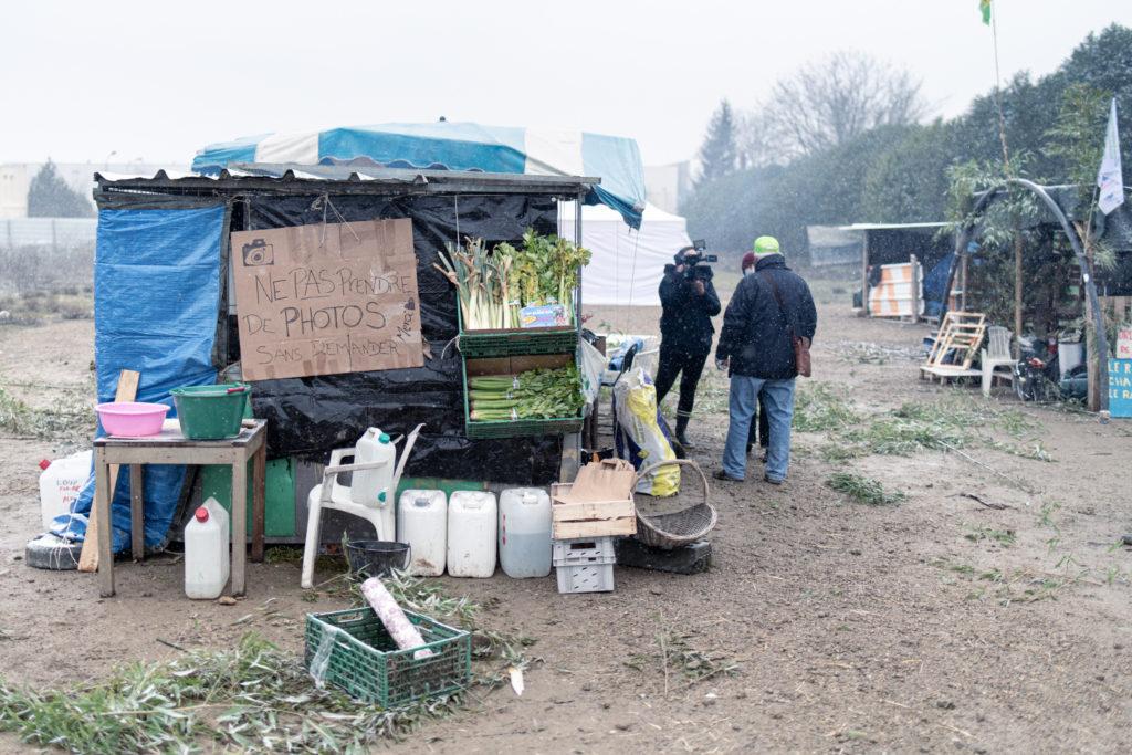 Un militant du Collectif pour le Triangle de Gonesse est interviewé par France 3 à côté de l'abri utilisé pour cuisiné sur la ZAD