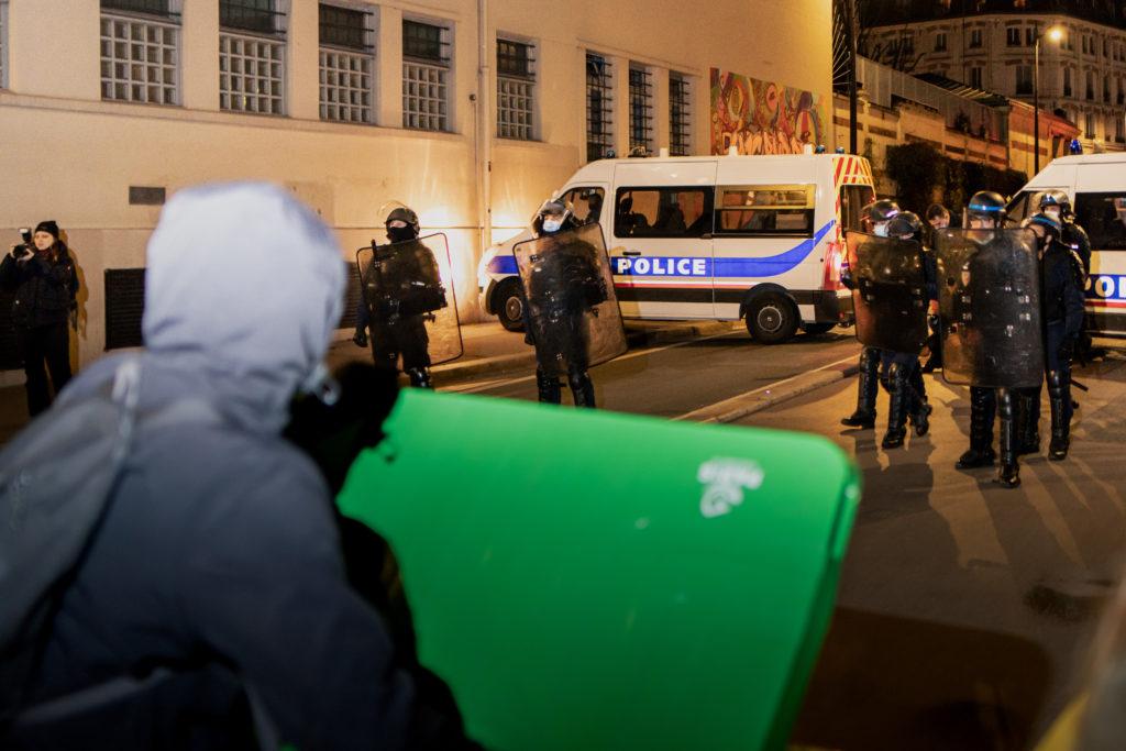 Des lycéens font face à la police avec des poubelles devant le lycée Colbert dans le 10ème arrondissement de Paris lors d'une tentative de blocus le 26 janvier 2021