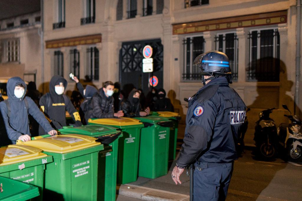 Un policier parlementente avec les lycéens qui souhaitent bloquer le lycée Colbert dans le 10ème arrondissement de Paris le 26 janvier 2021