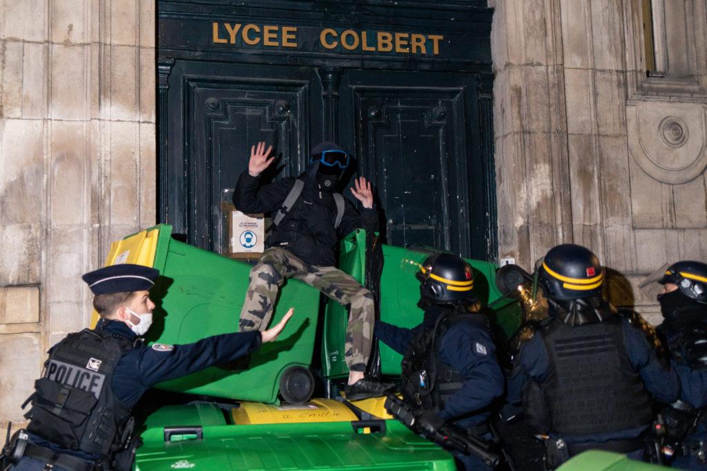 Un policier intime aux CRS de ne pas descendre trop brusquement un lycéen d'une pile de poubelle lors de la tentative de blocus du lycée Colbert dans le 10ème arrondisssement de Paris le 26 janvier 2021