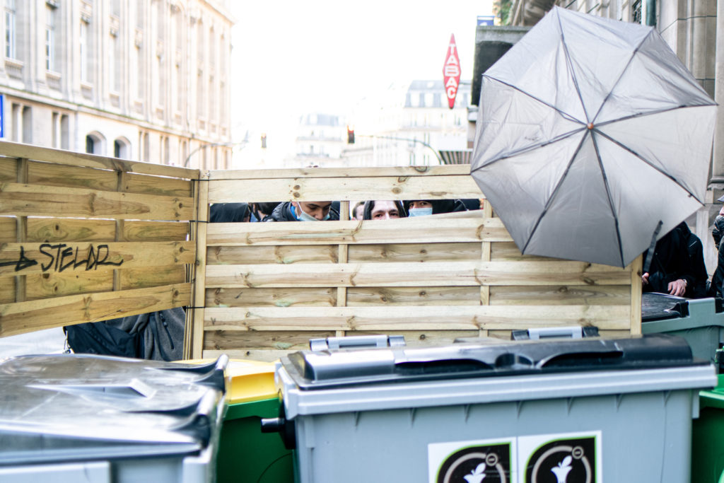 Des lycéens observent les mouvement des forces de l'ordre par les trous de leur barricade devant le lycée Racine à Paris le 26 janvier 2021