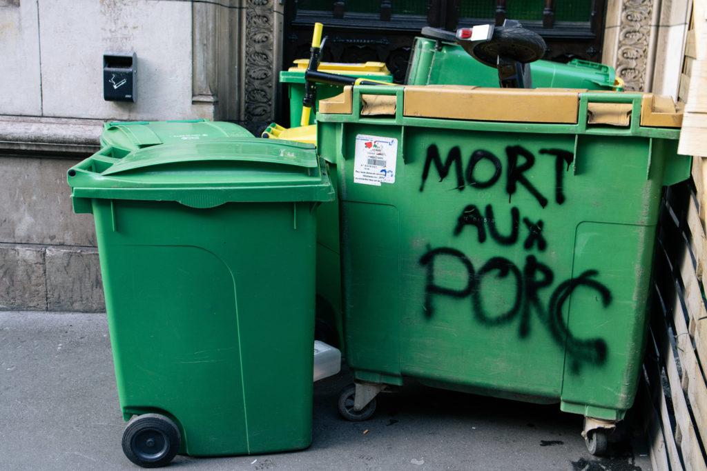 """Des poubelles, dont une avec un tag """"mort aux porc"""" suite à une tentative de blocus au lycée Racine à Paris le 26 janvier 2021"""